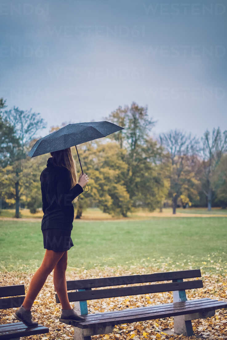 Young woman with umbrella balancing on two benches in autumnal park - JSCF00031 - Jonathan Schöps/Westend61