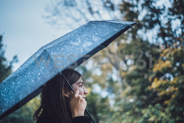 Young woman with wet umbrella in autumnal park - JSCF00034 - Jonathan Schöps/Westend61