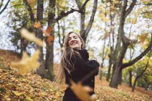 Portrait of happy young woman throwing autumn leaves in the air - JSCF00040