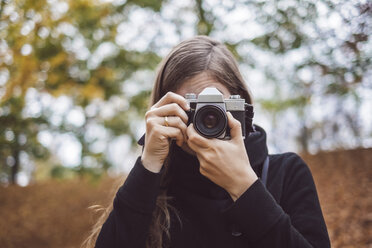 Portrait of young woman taking photos in autumn - JSCF00043