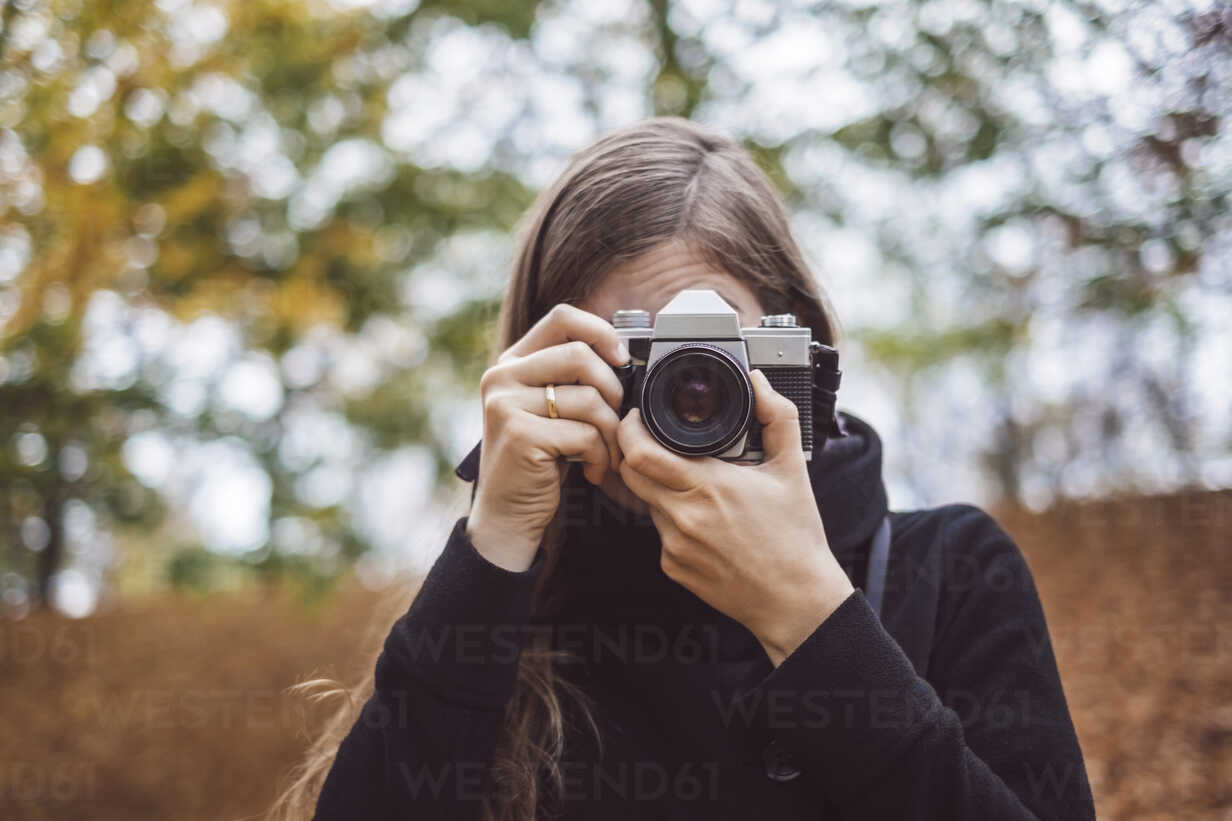 Portrait of young woman taking photos in autumn - JSCF00043 - Jonathan Schöps/Westend61