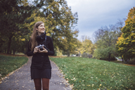 Young woman with camera walking in autumnal park - JSCF00046