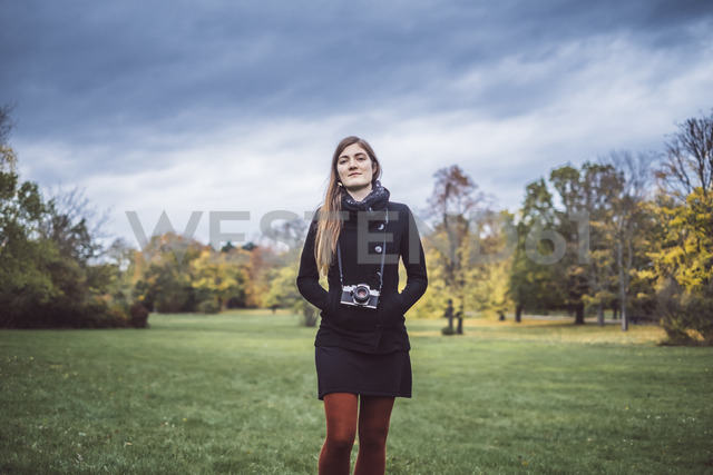 Portrait of young woman with camera walking on a meadow in autumnal park - JSCF00049