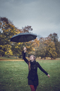 Happy young woman dancing with umbrella in autumnal park - JSCF00052