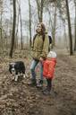 Germany, Mannheim, mother and daughter with border collie in the woods - DWF00321