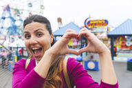 USA, New York, portrait of excited woman at Coney Island shaping heart with her hands - WPEF00041