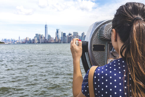 USA, New York, woman looking at Manhattan skyline with coin-operated binoculars - WPEF00044