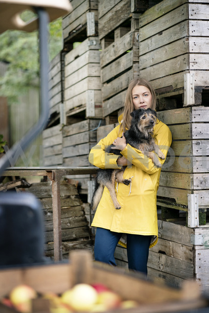 Woman on a farm standing at wooden boxes holding dog - PESF00958 - Peter Scholl/Westend61
