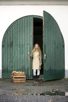 Woman on a farm standing at crate with apples - PESF00967