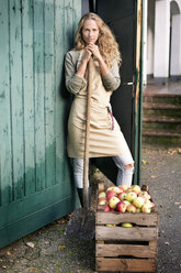 Portrait of confident woman standing at crate with apples - PESF00970