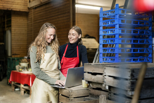 Two happy women using laptop between crates on a farm - PESF00976
