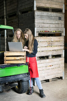 Two women using laptop between crates on a farm - PESF00979