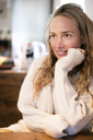 Portrait of smiling blond woman leaning on table - PESF00982
