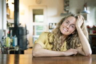 Portrait of smiling blond woman leaning on table - PESF00985