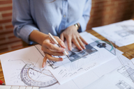 Young woman working in architecture office, drawing blueprints - VABF01478