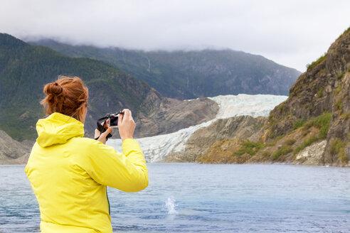 USA, Alaska, Juneau, female tourist photographing Mendenhall Glacier - MMAF00247