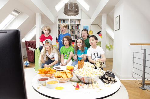 Group of kids watching soccer world championship with table full of sweets and snacks - NEKF00016