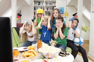 Group of kids watching soccer world championship with table full of sweets and snacks - NEKF00019