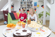Brother and sister watching football world cup with sweets and snacks - NEKF00022