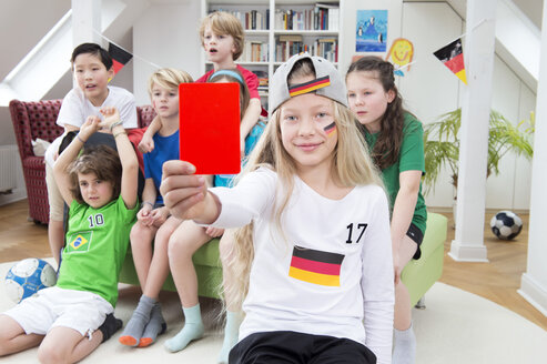Girl showing red card in front of friends, watching football world cup - NEKF00025