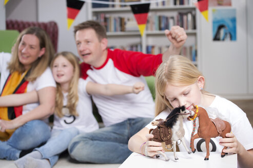 Family watching football world cup on TV, while little girl is playing with toys - NEKF00028