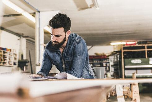 Man looking at draft in workshop - UUF12673