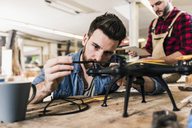 Man working on drone in workshop - UUF12679