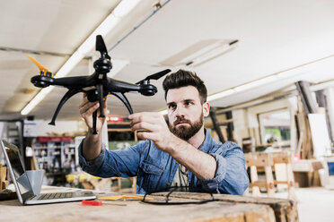 Man working on drone in workshop - UUF12682