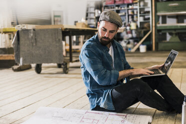 Man with laptop sitting on the floor looking at construction plan - UUF12694
