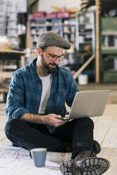 Smiling man with laptop and construction plan sitting on the floor - UUF12697