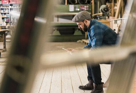 Man sitting in workshop using tablet - UUF12703