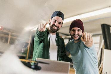 Portrait of two happy young men in workshop - UUF12709