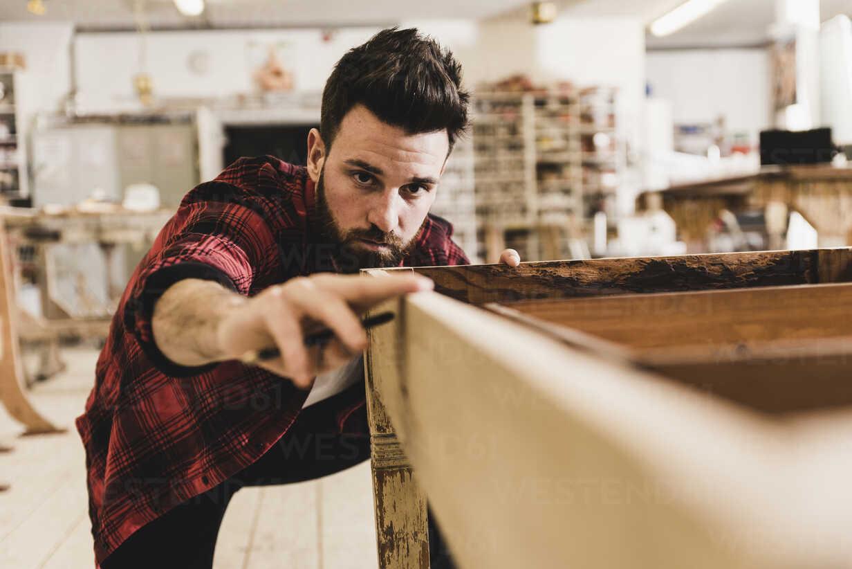 Man examining wood in workshop - UUF12715 - Uwe Umstätter/Westend61