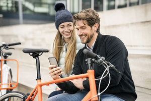 Smiling couple with bicycles and cell phone in the city - PESF00996