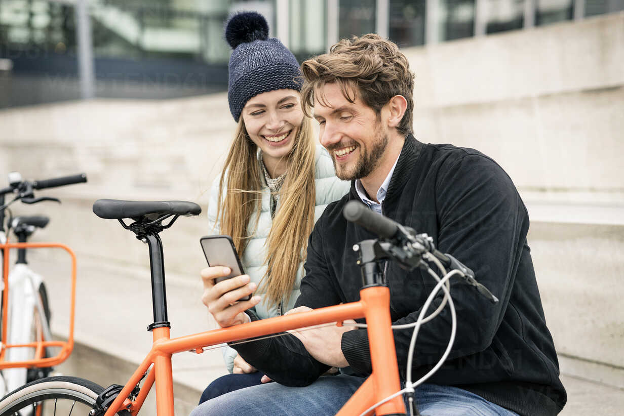 Smiling couple with bicycles and cell phone in the city - PESF00996 - Peter Scholl/Westend61