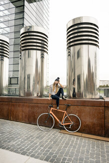 Young woman with bicycle having a break in the city - PESF00999