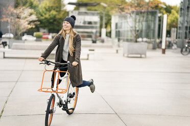 Happy woman riding bicycle in the city - PESF01002