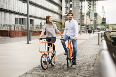 Smiling couple riding bicycle in the city - PESF01005
