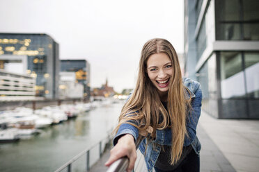 Portrait of laughing young woman at city harbor - PESF01011