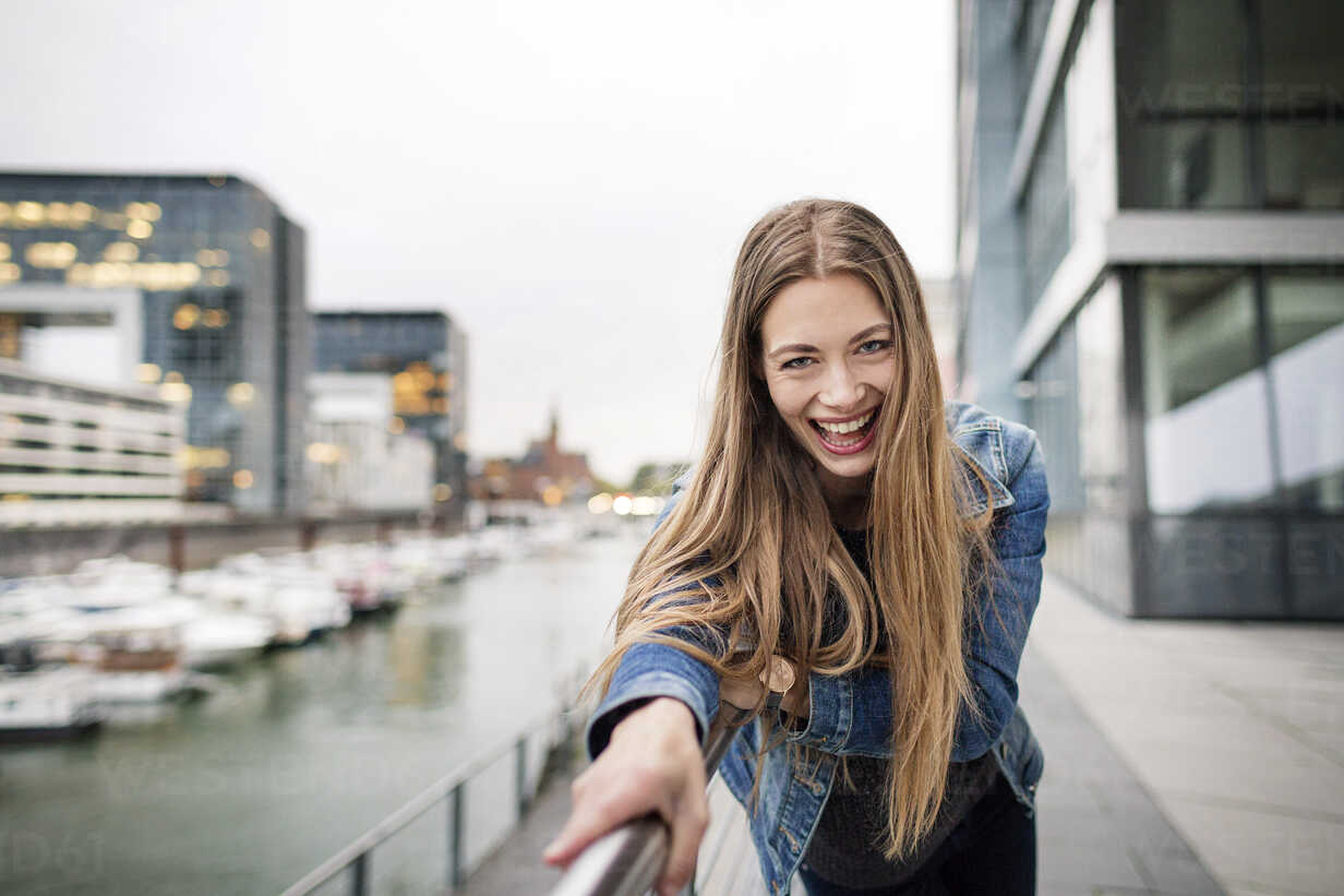 Portrait of laughing young woman at city harbor - PESF01011 - Peter Scholl/Westend61