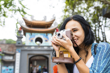 Vietnam, Hanoi, young woman taking a picture with old-fashioned camera - WPEF00054