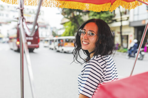 Vietnam, Hanoi, portrait of smiling young woman on a riksha in the city - WPEF00060