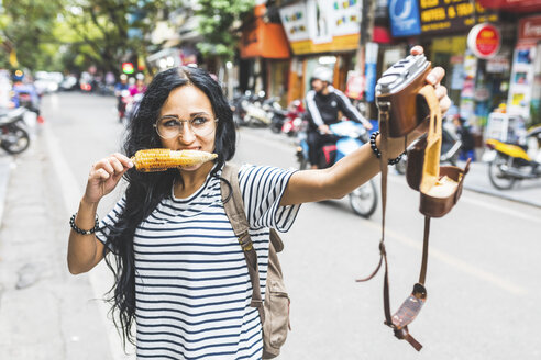 Vietnam, Hanoi, young woman taking a selfie with old-fashioned camera on the street eating a corn cob - WPEF00063