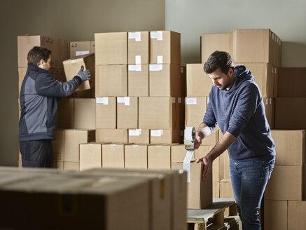 Workers closing packages with package tape - CVF00108