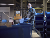 Worker putting boxes on conveyor belt - CVF00117