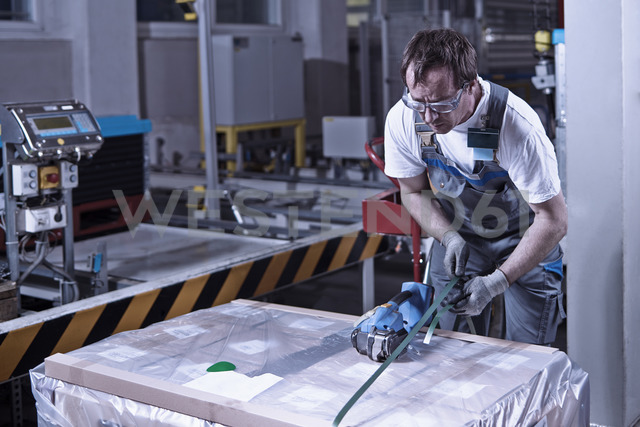 Worker closing freight with foil - CVF00123 - Christian Vorhofer/Westend61