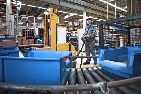 Man at work in factory with boxes on conveyor belt - CVF00126