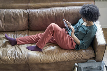 Young woman lying on couch using tablet - FMKF04801