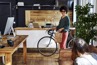 Young woman with bicycle arriving in modern office - FMKF04813