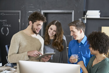 Smiling coworkers sharing tablet in office - FMKF04825